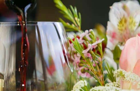 Close up view of wine glass with red wine pouring into it next to white, pink, and yellow flowers