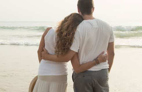 Man and woman with arms around each other standing in water on beach looking at the waves