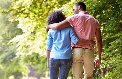 Man and woman with arms wrapped around each other walking near greenery