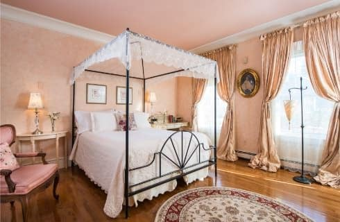 Bedroom with rod iron four-post canopy bed with white bedding, light colored wooden desk and chair in the corner, hardwood floors, peach floral wallpaper with peach drapery