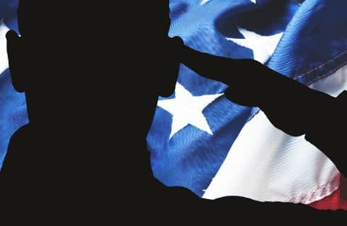 Black silhouette of soldier saluting in front of United States flag