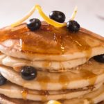 Tall stack of pancakes with syrup and blueberries on top and a side of bacon on a white porcelain plate