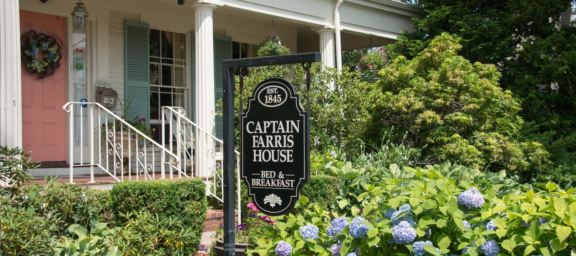Front view of property with salmon-colored door and light turquoise shutters surrounded by shrubs, bushes, and flowers with a sign for Captain Farris House