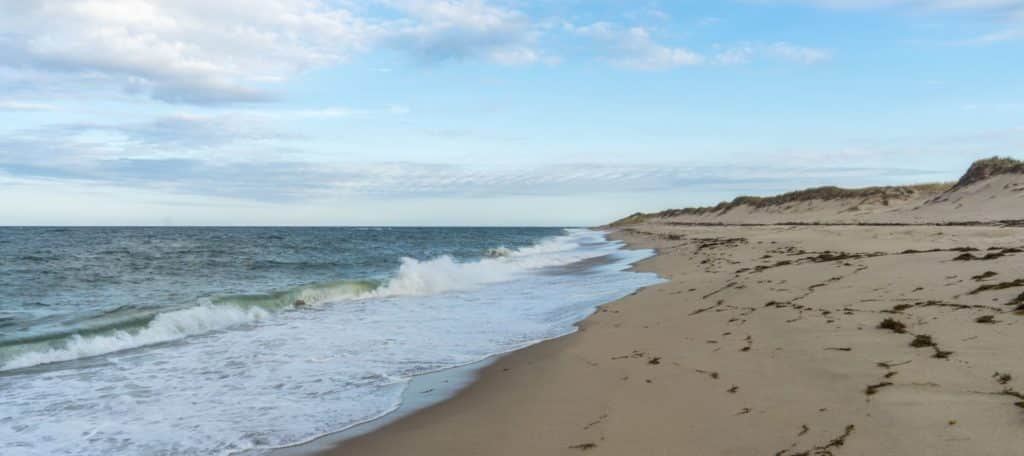 View of a sandy beach with dunes next to the ocean with gently rolling waves crashing on the beach