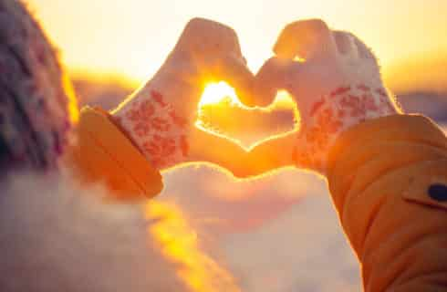 Someone making a heart with mitten-covered hands during a winter sunset