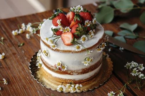 Small white frosted wedding cake with strawberries and daisies