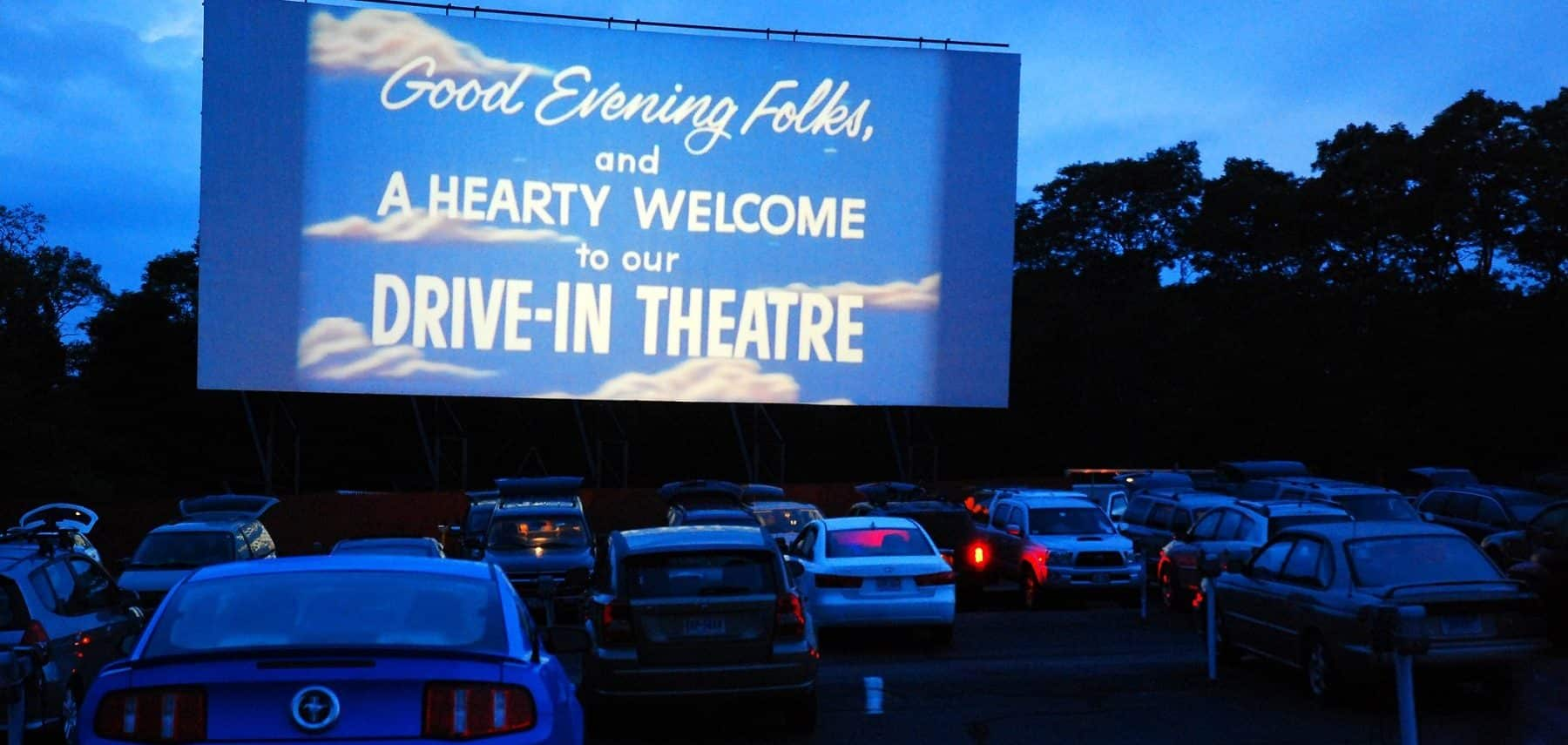 "Cars parked in front of the Wellfleet Drive-In Theatre with the screen displaying ""Good Evening Folks, and a Hearty Welcome to our Drive-In Theatre"""